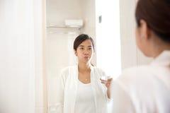 Азиатский gargle молодой женщины на ее рте после чистить щеткой зуба стоковое изображение