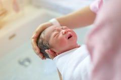 Азиатский newborn купать его матерью Стоковая Фотография