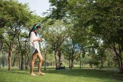 Азиатский smartphone игры девушки в парке Стоковая Фотография