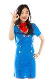 Азиатский stewardess воздуха показывая одобренный знак изолированный на белой предпосылке стоковое изображение