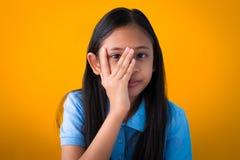 Азиатским шаловливым предпосылка девушки изолированная портретом оранжевая стоковое изображение rf