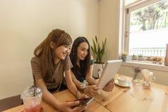 2 азиатских девушки используют таблетку пока сидящ в кафе и выпивая кофе Стоковые Фотографии RF
