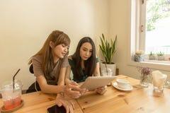 2 азиатских девушки используют таблетку пока сидящ в кафе и выпивая кофе Стоковое фото RF