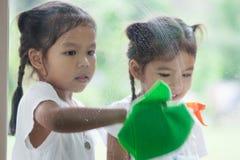 2 азиатских девушки маленьких ребенка помогают родителю очистить окно Стоковая Фотография RF