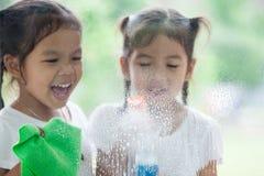 2 азиатских девушки маленьких ребенка помогают родителю очистить окно Стоковые Фотографии RF
