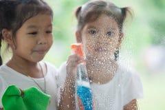 2 азиатских девушки маленьких ребенка помогают родителю очистить окно Стоковое Изображение RF