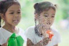 2 азиатских девушки маленьких ребенка помогают родителю очистить окно Стоковое Изображение