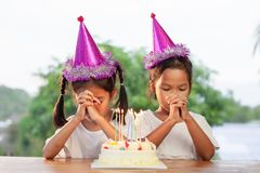 2 азиатских девушки ребенка делают сложенную руку для того чтобы пожелать хорошие вещи их день рождения стоковые фото