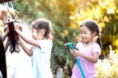 2 азиатских девушки ребенка имея потеху для того чтобы помочь родительскому моя автомобилю Стоковые Фото