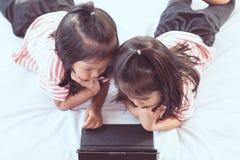 2 азиатских девушки ребенка имея потеху для того чтобы сыграть игру в цифровой таблетке Стоковые Изображения