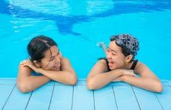 2 азиатских девушки беседуют в плавательном бассеине Стоковая Фотография