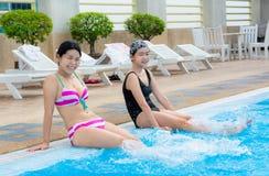 2 азиатских девушки брызгают воду на плавательном бассеине Стоковая Фотография