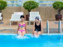 2 азиатских девушки брызгают воду на swimmin Стоковые Изображения RF