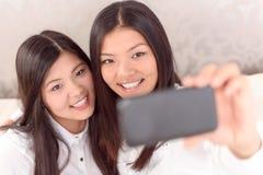 2 азиатских девушки делая selfie Стоковые Изображения