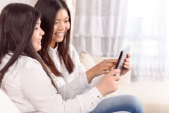 2 азиатских девушки играя на таблетке Стоковая Фотография