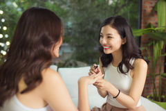 2 азиатских девушки крася toenails и ногти на кровати в li Стоковые Фото