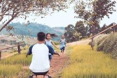 2 азиатских девушки маленьких ребенка бежать к их отцу Стоковая Фотография