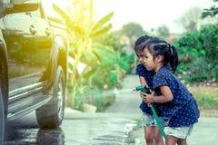 2 азиатских девушки помогая родителю моя автомобиль Стоковая Фотография RF