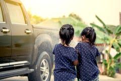 2 азиатских девушки помогая родителю моя автомобиль Стоковые Фотографии RF