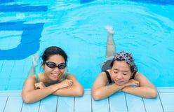 2 азиатских девушки расслабляющие в угле бассейна Стоковая Фотография RF