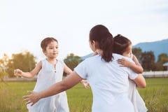 2 азиатских девушки ребенка бежать к их матери для того чтобы дать объятие Стоковое фото RF