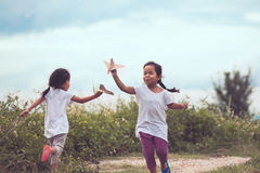 2 азиатских дет играя с airplanep бумаги игрушки Стоковое фото RF