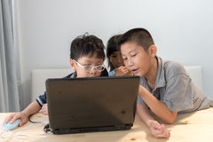 3 азиатских дет используя компьтер-книжку дома Стоковые Изображения