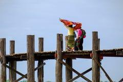 2 азиатских женщины в красочных одеждах идя на деревянный мост Стоковые Изображения