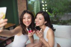 2 азиатских женщины в спальне на кровати красят их ногти и стоковое фото