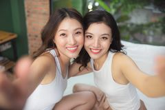2 азиатских женщины в спальне на кровати красят их ногти и Стоковое Изображение