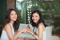 2 азиатских женщины в спальне на кровати красят их ногти и Стоковое Изображение RF