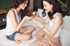 2 азиатских женщины в спальне на кровати красят их ногти и Стоковая Фотография RF