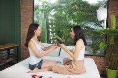 2 азиатских женщины в спальне на кровати красят их ногти и Стоковые Изображения RF