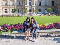 2 азиатских женщины изучают сотовый телефон в Люксембургском саде, Париже Стоковые Фотографии RF