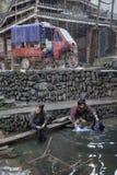 2 азиатских женщины полощут прачечную в деревне реки, Китае Стоковые Фото