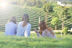 3 азиатских женщины сидят на траве и мобильном телефоне игры в саде o Стоковые Изображения RF