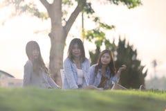 3 азиатских женщины сидят на траве на sunnyday Стоковая Фотография