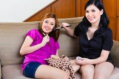 2 азиатских индонезийских девушки самонаводят используя составляют Стоковое Изображение