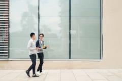 2 азиатских люд говорят и используют умный телефон вне здания] Стоковое Изображение
