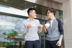 2 азиатских люд говорят и используют умный телефон вне здания Стоковые Изображения RF