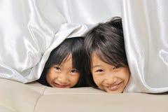 2 азиатских маленького ребенка peeking вне от занавеса Стоковые Фото
