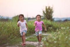 2 азиатских маленькой девочки имея потеху и ход совместно Стоковое фото RF
