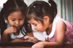 2 азиатских маленькой девочки имея потеху, который нужно наблюдать на таблетке совместно Стоковые Изображения RF