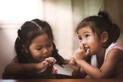 2 азиатских маленькой девочки имея потеху, который нужно наблюдать на таблетке совместно Стоковое фото RF