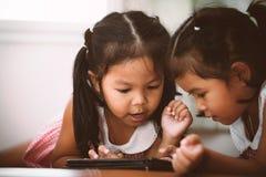 2 азиатских маленькой девочки имея потеху, который нужно наблюдать на таблетке совместно Стоковое Изображение