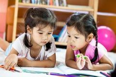 2 азиатских маленькой девочки имея потеху, который нужно покрасить с crayon Стоковые Фото