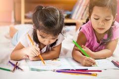 2 азиатских маленькой девочки имея потеху, который нужно покрасить с crayon Стоковое фото RF