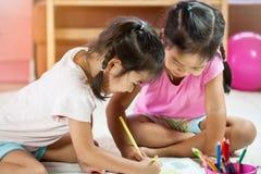 2 азиатских маленькой девочки имея потеху, который нужно покрасить с crayon Стоковая Фотография RF
