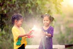2 азиатских маленькой девочки имея потеху для того чтобы сыграть воду совместно Стоковые Изображения RF