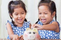 2 азиатских маленькой девочки имея потеху для установки монетки в копилку Стоковое Изображение